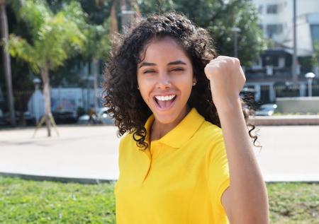 liberated: Cheering latin american girl with long dark hair Stock Photo