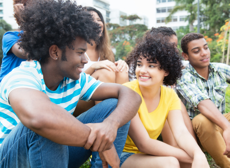 African guy speaking with girlfriend outdoor with multiethnic group
