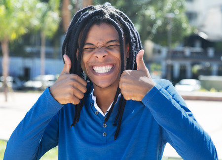 jamaican man: Young guy with dreadlocks showing both thumbs in the city