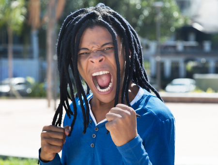 jamaican man: Cheering guy with dreadlocks in the city