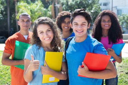 Groupe de cinq étudiants latin, américain, caucasien et africains intelligents de plein air dans la ville en été