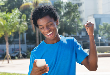 online bidding: Young african american man receiving good news at mobile phone