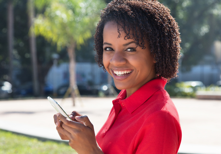latina america: Laughing african american woman sending message with mobile