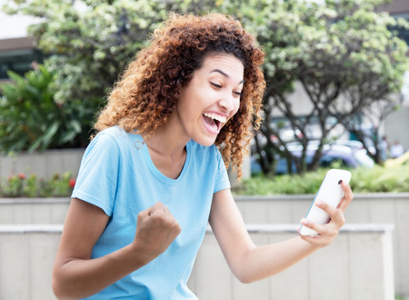 Cheering mexican girl receiving good news at phone  outdoor in city Stock Photo