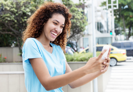 Happy mexican girl receiving good news at phone  outdoor in city Stock Photo