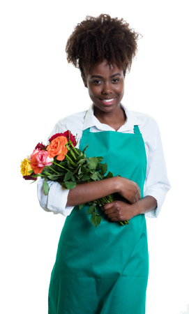 Laughing african american female florist with curly hair and green apron