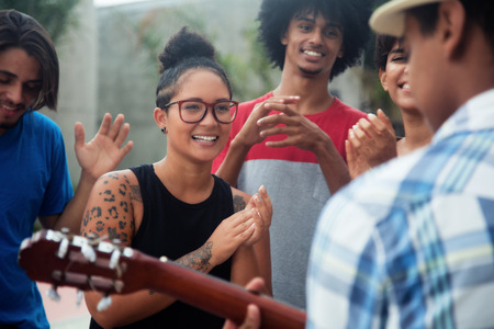Young people listening to a concert of a muscian outdoor in the city Stock Photo