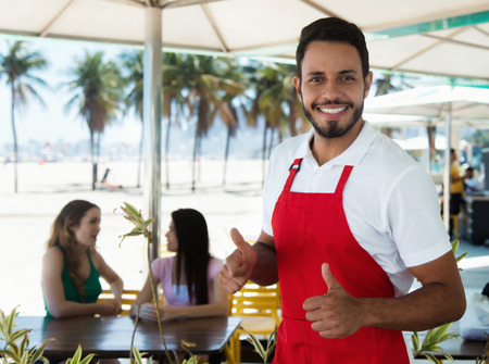 Laughing waiter of a cocktail bar at beach