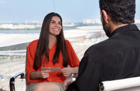 Latin female presenter asking a famous celebrity at tv studio Stockfoto