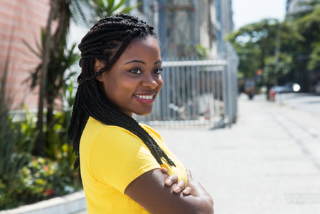 Smiling african american woman in yellow shirt looking sideways