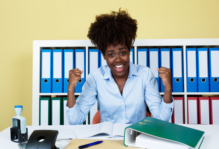 trusty: Cheering african american businesswoman working at office