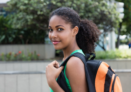 Smiling latin female student with bag in the city