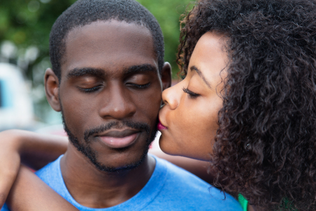 African american woman kissing boyfriend in summer