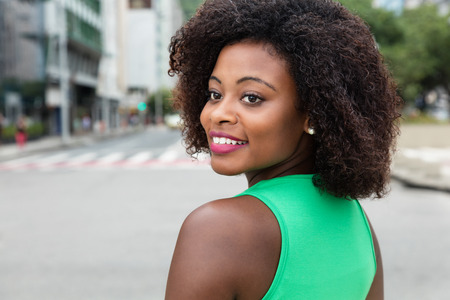 Beautiful woman from Africa looking back in the city