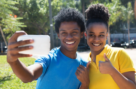 Young african american man with latin woman taking selfie with phone outdoor in city in summer
