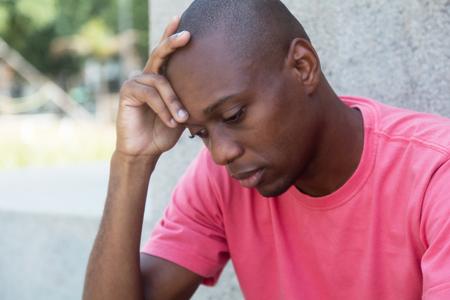 Hombre afroamericano sin pelo en la depresión al aire libre en el verano Foto de archivo