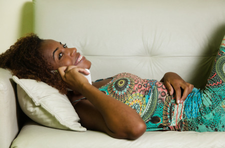 Laughing african american woman speaking at phone on sofa at home in living room