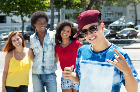 Chico cool hip hop con grupo de amigos caucásicos y afroamericanos al aire libre en el verano en la ciudad Foto de archivo
