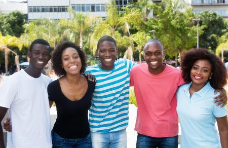 Groep van Afrikaanse-Amerikaanse man en vrouw die in de zomer in de stad loopt Stockfoto