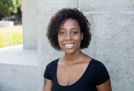 African american woman with black shirt looking at camera outdoor in the summer