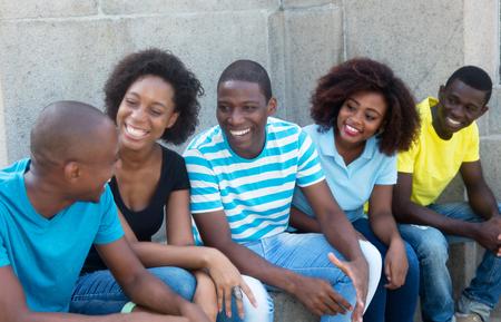 Sprekende groep Afrikaanse Amerikaanse mannen en vrouwen in openlucht in de zomer Stockfoto