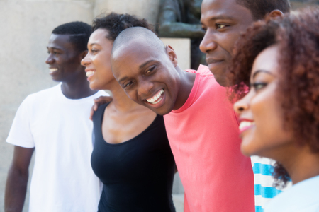 Group of relaxing african american men and women outdoors in the summer