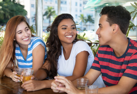 Two young woman talking with a guy in a bar at the first date Imagens