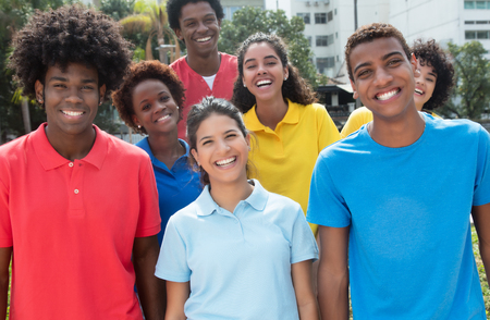 Large group of mixed young adults in colorful shirts outdoor in the summer