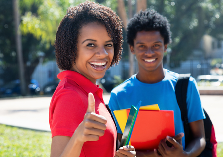African american female student showing thumb with african male student outdoor on campus of university