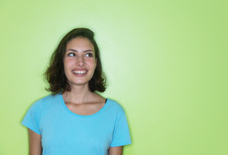 Young caucasian woman looking sideways to a green wall for advertising