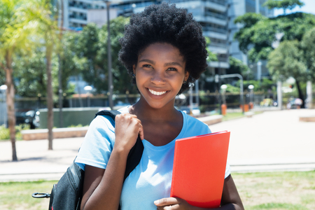 Laughing african american female student looking at camera on campus of university Stock Photo