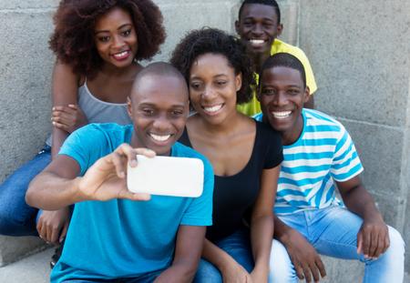 Groep van vijf Afro-Amerikaanse mannen en vrouw nemen selfie met slimme telefoon
