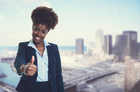 African american businesswoman showing thumb with skyline of city in the background