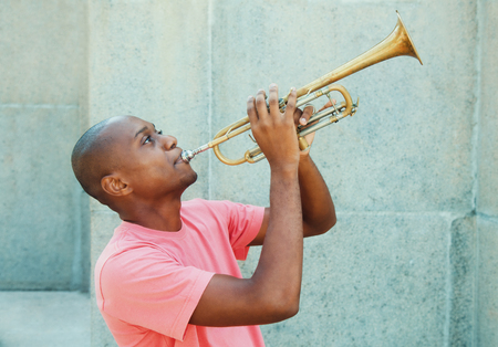 African american artist with trumpet outdoor in the summer