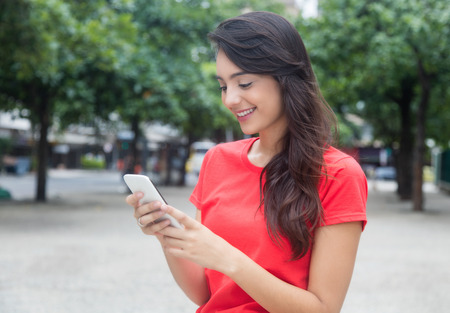 Beautiful girl with red shirt surfing the net with phone outdoor in the city in the summer