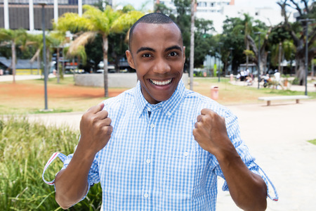 Successful cheering african american man Stock Photo