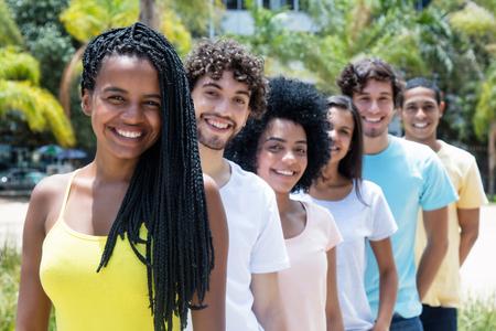 Mooie Afrikaanse Amerikaanse vrouw met dreadlocks met multi-etnische vrienden in lijn Stockfoto