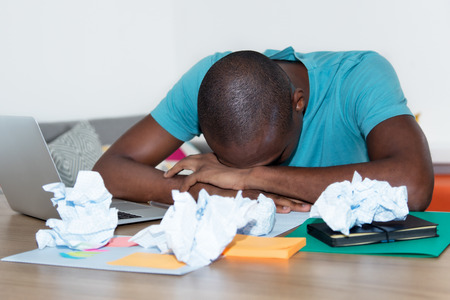 Sleeping African American man at desk at home office
