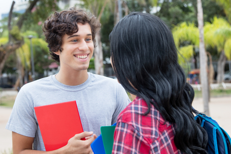 Caucasian male student talking with native latin american girlfriend