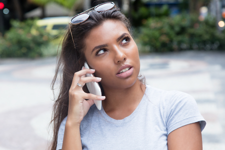 Latin female teenager listening at smart phone outdoor in the summer in the city Stock Photo