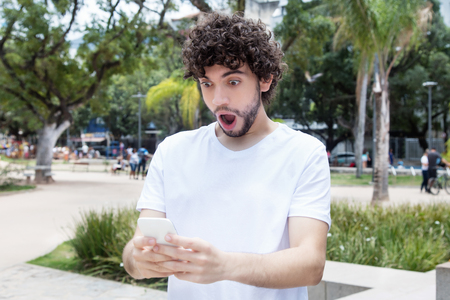 Surprised young adult hipster with cellphone receiving message