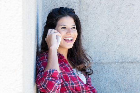 Caucasian woman in casual clothes laughing at phone