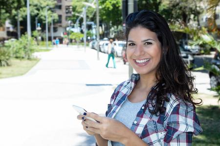 Beautiful caucasian woman using phone in city