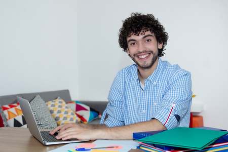 Handsome caucasian hipster working at home with computer Stock Photo