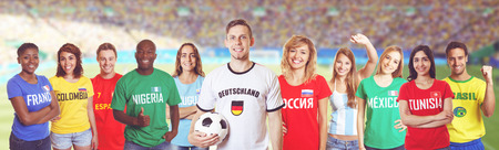 German soccer fan at stadium with group of fans from other countries