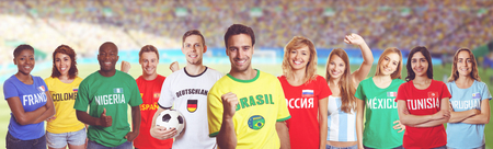 Brazilian soccer fan at stadium with group of fans from other countries Stock Photo