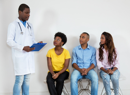 African american doctor with patients at waiting room
