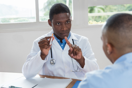 Médico afroamericano recomendando no fumar