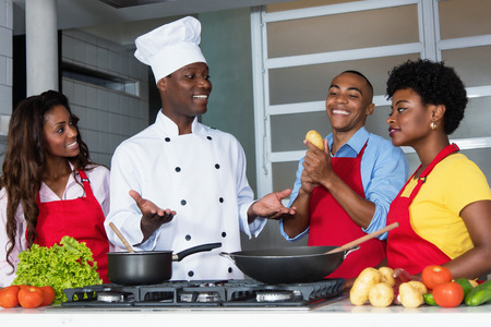 African american chef teaching women and men at kitchen