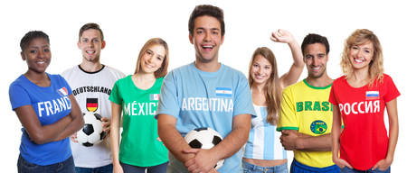 Argentinian soccer fan with ball and cheering group of other fans